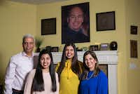 The Valliani family -- from left, Farrukh, Alisha, Shireen and Farida -- in their home in Irving. They are members of the Ismaili faith and traveled to Houston to see their spiritual leader, the Aga Khan, who is pictured above their mantel.(Ashley Landis/Staff Photographer)
