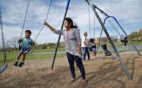 "<p><br><span style=""font-size: 1em; background-color: transparent;"">Asrav Anand, 4, swings on the swingset with his mother, Sumit Kumari, at Thomas Jefferson Park in Irving.</span><br></p><p><br></p>(Nathan Hunsinger/Staff Photographer<div><br></div>)"