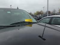 "DART ""Ridership Alerts"" were placed on windshields Friday at the Downtown Rowlett Station, alerting people to the change to priority parking there.(Staff/Ray Leszcynski)"