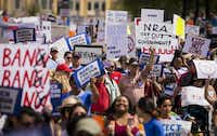 Demonstrators march down Young Street near City Hall during a rally and march in support of gun safety laws.(Smiley N. Pool/Staff Photographer)