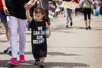 """18-month-old Henry Ayers wears a shirt reading """"We Can End Gun Violence"""" as he walks with his family during a rally and march in support of gun safety laws.(Smiley N. Pool/Staff Photographer)"""