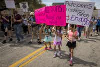 A group of young girls carry signs in both English and Spanish.(Smiley N. Pool/Staff Photographer)