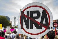 A demonstrator carries a sign in opposition to the National Rifle Association.(Smiley N. Pool/Staff Photographer)