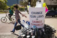 Protest signs and water bottles fill a sidewalk trash bin after a rally and march in support of gun safety laws.(Smiley N. Pool/Staff Photographer)