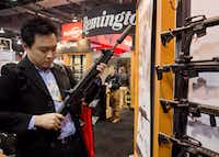 Accessories manufacturer Kevin Kao, of Irvine, Calif., examines a military grade Remington Adaptive Combat Rifle at the 35th annual SHOT Show in Las Vegas. U.S. gun maker Remington Outdoor Company filed for bankruptcy protection, after years of falling sales and lawsuits tied to the Sandy Hook Elementary School massacre.(Julie Jacobson/AP)