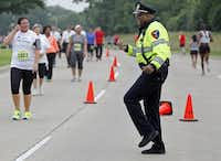 Arthur Parker, the school resource officer at Clark High School in Plano, entertains runners at an event in May 2015.(2015 File Photo/Staff)