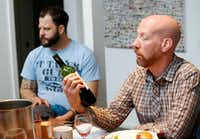 James Tidwell (right) reads the back of a wine bottle during a wine panel tasting with chef Chad Houser.(Vernon Bryant/Staff Photographer)
