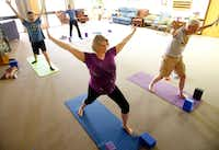 Senior pastor Valarie Englert (in purple) and congregation members Tom Hilbun (back) of Garland, Ann McMann of Garland and David Barton participate in a yoga class held at the First United Methodist Church in Garland.(Tom Fox/Staff Photographer)