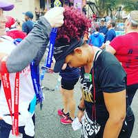 Daphne Jackson, who says running has brought her closer to God, bows her head to receive a medal from one of the many half marathons she's completed since beginning her journey.