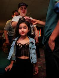 Selena fan Daniella Alvarado, 5, is all  dressed up like her idol for the 7 p.m. showing March 21, 1997, at the AMC Grand at the corner of Northwest  Highway and Stemmons Expressway. Her mom, Clara Alvarado, is  behind her, giving tickets to an usher. (Randy Eli Grothe/The Dallas Morning News)