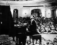 In this photo provided by the Van Cliburn Foundation, Texas pianist Van Cliburn performs to a packed audience in the Great Hall of the Moscow Conservatory in Moscow, Russia, in April 1958 during the first International Tchaikovsky Competition, which he won.(Anonymous/AP)