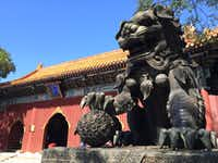 The statue of a dragon-like beast guards one of the buildings at Yonghe Temple in Beijing in September 2017.(Thomas Huang/The Dallas Morning News)