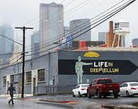 An appropriate sign on a Deep Ellum building is pictured with part of the downtown Dallas skyline in the background during a rainy day. (Louis DeLuca/Staff Photographer)