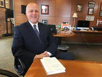 "New Orleans Mayor Mitch Landrieu poses with a copy of his new book, ""In the Shadow of Statues"" in New Orleans in March. The book is a memoir in which Landrieu discusses the issues of race that affected his personal and political life, and his role in the removal of four Confederate-related monuments from the city landscape.(Kevin McGill/AP)"