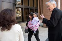 Lucia Mejia, carrying her 19-month-old daughter Teresa, is accompanied by Auxiliary Bishop Greg Kelly (right) and other supporters from her parish as she enters the Earle Cabell Federal Building to watch a video feed of a court hearing for her husband, who was detained by Immigration and Customs Enforcement. (Jeffrey McWhorter/Special Contributor)