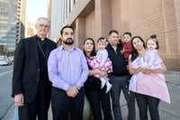 Lucia Mejia, wife of Adolfo Mejia (center), holds her 19-month-old daughter, Teresa Mejia, as she is surrounded by friends and supporters (from left) Auxiliary Bishop Greg Kelly; godfather to Teresa Mejia, Daniel Casiamano; friends Horacio and Maura Ortega, holding their son Emmanuel and daughter Genesis. They stand outside the Earle Cabell Federal Building before a court hearing for her husband.(Jeffrey McWhorter/Special Contributor)