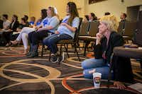 Environmental activist Erin Brockovich sits on the floor and listens as water consultant Bob Bowcock addresses a town hall style meeting at Frisco Celebration Hall on Thursday.(Smiley N. Pool/Staff Photographer)