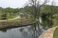 The Farmers Branch creek flows by an exercise trail in Vitruvian Park in Addison, Texas. (Louis DeLuca/Staff Photographer)