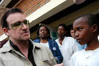 Irish rock star Bono meets an unidentified boy at a health center in Mayange, Rwanda. (RICCARDO GANGALE/AP)