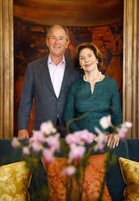 Former President George W. Bush and First Lady Laura Bush pose before a painting of the Grand Canyon by artist Adrian Martinez in the Presidential Reception Hall at the George W. Bush Presidential Center.(Tom Fox/Staff Photographer)