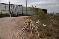Ladders used by immigrants to scale walls and levees sit by the border fence near McAllen, Texas.(Lynsey Addario/The New York Times)