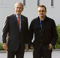 Former President George W. Bush walks with Bono (R) in June 2007 before a meeting at the on the Baltic Sea resort of Heiligendamm, northeastern Germany.(MANDEL NGAN/AFP/Getty Images)