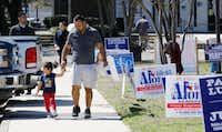 Armando Vergara walks his daughter Evylin, 3, past the Dallas County Government Center, Precinct 5 in Oak Cliff on Election Day.(David Woo/Staff Photographer)