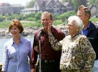 "<p>Barbara Bush playfully slaps her son George during a photo op at the family home <span style=""font-size: 1em; background-color: transparent;"">in Kennebunkport, Maine, in June 1999. George W. Bush, standing with his wife, Laura, was Texas governor at the time.</span></p>(1999 File Photo)"