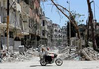Syrians ride a motorbike along a destroyed street in Douma on the outskirts of Damascus on April 16, 2018 during an organised media tour after the Syrian army declared that all anti-regime forces have left Eastern Ghouta, following a blistering two month offensive on the rebel enclave.   The announcement, which represents a key strategic victory for President Bashar al-Assad, came just hours after US-led strikes pounded Syrian government targets in response to a suspected chemical attack on the enclave's main town of Douma. (LOUAI BESHARA/AFP/Getty Images)