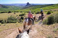Guests ride on a trail at Smith Fork Ranch with the unique Needle Rock in the background. (Michaela Urban/Special Contributor)