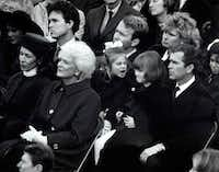 Barbara Bush watches as her husband George H.W. Bush is inaugurated president of the United States on Jan. 20, 1989. Behind her, George W. Bush holds his daughter Jenna, 7,  on his lap as she and her cousin Lauren Bush, 4, (on the lap of her father, Neil) have a disagreement.(David Woo/Staff Photographer)