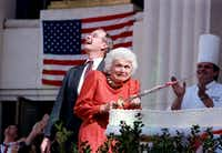 Barbara Bush cringes as a low-flying jet ceremonially passes overhead during cake-cutting ceremonies for the Texas sesquicentennial held at Fair Park on March 2, 1986. At the time, her husband, standing behind her, was vice president.(Staff/1986 File Photo)