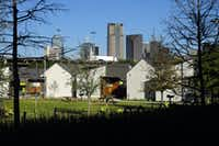The Dallas skyline rises above the Cottages at Hickory Crossing, which are located on the southeast corner of Interstate 35E and Interstate 45 in Dallas.(Tom Fox/Staff Photographer)