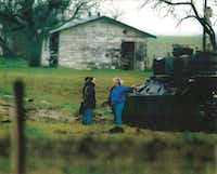 FBI negotiator Byron Sage (front right, in blue) and McLennan County Sheriff Jack Harwell (obscured behind Sage, in white hat), stoodg next to a tank while talking to Branch Davidians Steve Schneider and Wayne Martin during the standoff.(FBI)