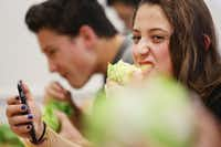 Senior Cammy Rodriguez bites into a head of lettuce during a meeting of The Lettuce Club at Heritage High School on Tuesday in Frisco.(Andy Jacobsohn/Staff Photographer)