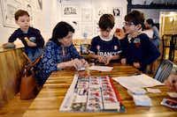 Carmen de Paoli works with a group of kids organizing Panini stickers, including Sebastian del Porto, 4, left, Nicolas del Porto, 8, and Nicolas Lamus, 7, right, at a Panini World Cup sticker album exchange event at Arepa TX in Dalla(Ben Torres/Special Contributor)