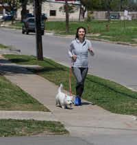 Aly Christensen, walks her dog, Coconut, along  the 2100 block of North Henderson Avenue in Dallas on April 5, 2018. A Dallas developer wants to build a mixed-use development on a stretch of land off of Henderson Avenue that has been vacant for years. The lot is between Glencoe Street to McMillan Avenue. She is in favor of the proposed development.  (Ron Baselice/Staff Photographer)