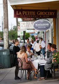 A waitress takes an order from a table outside La Petite Grocery on Magazine Street in the Touro neighborhood of New Orleans.(Rose Baca/Staff Photographer)