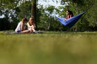 "Friends (from left) Schuler Ravencraft, Tess Martin and Haley Ginsberg relax as the sun sets at Riverview Park, or ""The Fly,"" as New Orleans locals call it.(Rose Baca/Staff Photographer)"