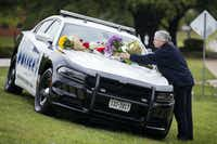 Marcia Niemann placed flowers on a Dallas police car in honor of Officer Rogelio Santander on April 25, 2018, outside the Dallas Northeast Patrol Division. Niemann lives close to the police substation.(Ashley Landis/Staff Photographer)