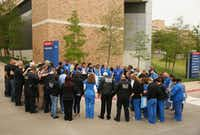Members of the Dallas Police Department and hospital personnel pray outside Texas Health Presbyterian Dallas.(Andy Jacobsohn/Staff Photographer)