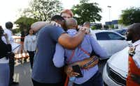 Friends and employees comforted one another outside Home Depot after two officers and a civilian were shot April 24, 2018.(Tom Fox/Staff Photographer)
