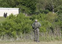 Dallas police looked for a suspect in the shooting of two officers and a civilian on April, 24, 2018, in the woods near the Home Depot on Forest Lane.(Ron Baselice/Staff Photographer)