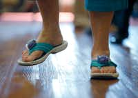 Betty Means wears step counters on her sandals during a line dancing class.(Nathan Hunsinger/Staff Photographer)