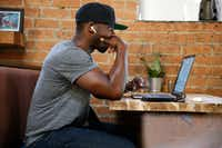 Collins Idehen, aka Colion Noir, works on his NRA TV show <i>NOIR</i>at a coffee shop in Deep Ellum.(Nathan Hunsinger/Staff Photographer)
