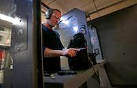 NRA TV anchor and reporter Grant Stinchfield checks his handgun after firing at DFW Gun Range in Dallas.(Jae S. Lee/Staff Photographer)