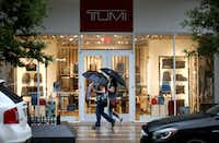 People walked past the Tumi store at Legacy West in Plano during a rain shower Thursday.of (Rose Baca/Staff Photographer)