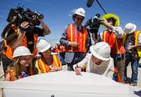 Margaret McDermott, right, signs a piece of the Margaret McDermott Bridge, which was named after her, flanked by Grace Cook, McDermott's granddaughter, left; Mary McDermott Cook, daughter of McDermott, and architect Santiago Calatrava during a bridge signing ceremony on June 11, 2015 in Dallas.(Ashley Landis/Staff Photographer)