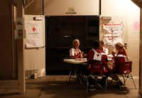 Red Cross volunteers sit at the entrance of an evacuation shelter Friday in Pahoa, Hawaii.(Marco Garcia/AP)