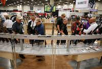 Men look at scopes at the NRA Annual Meeting & Exhibits at Kay Bailey Hutchison Convention Center in Dallas on Friday.(Rose Baca/Staff Photographer)